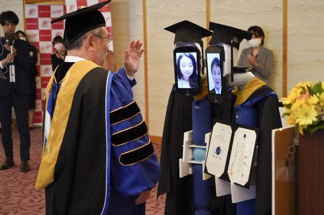 Para wisudawan mengoperasikan robot 'Newme' secara jarak jauh melalui aplikasi zoom.