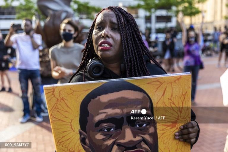 Seorang wanita bereaksi saat dia berbaris dalam sebuah acara untuk mengenang George Floyd di Minneapolis, Minnesota, pada 23 Mei 2021. Pendukung dan kerabat dari Afrika-Amerika George Floyd mulai berkumpul pada 23 Mei menjelang peringatan pertama kematiannya di bawah seorang polisi kulit putih. lutut, pembunuhan yang mendorong perhitungan ketidakadilan rasial di Amerika Serikat.