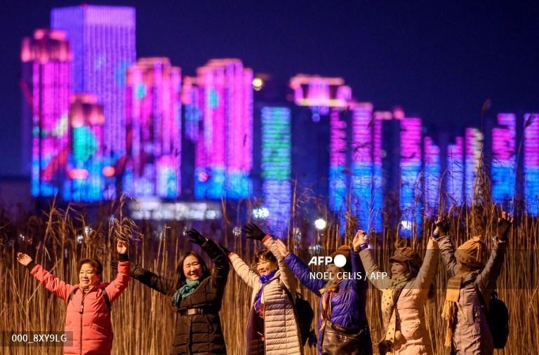 Orang-orang berpose untuk berfoto di tepi Sungai Yangtze pada Malam Tahun Baru di Wuhan, di provinsi Hubei tengah China pada 31 Desember 2020.