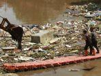 alat-berat-mengangkat-sampah-pasca-banjir-di-kali-sunter_20210222_185242.jpg
