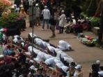 Massa Aksi Unjuk Rasa Kumpul di Patung Kuda, Salat Berjamaah di Trotoar Hingga Bagikan Masker