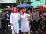 dua-orang-yang-mengenakan-baju-putih-dan-berambut-merah-demo-omnibus-sumsel.jpg