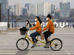 pasangan-yang-mengenakan-masker-naik-sepeda-tandem.jpg