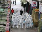 pekerja-pasar-mengenakan-disinfektan-semprotan-pelindung-di-sebuah-pasar-di-kota-tenggara-daegu.jpg