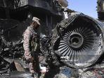 petugas-keamanan-berdiri-di-samping-puing-puing-pesawat-pakistan-international-airlines.jpg