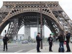 petugas-polisi-memeriksa-dokumen-seorang-pria-di-depan-menara-eiffel-di-paris.jpg
