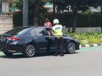 petugas-polisi-mengatur-penerapan-nopol-ganjil-genap-mobil_20211004_125317.jpg