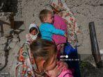 seorang-wanita-hazara-berdiri-bersama-anak-anak-di-sebuah-tebing-di-bamiyan.jpg
