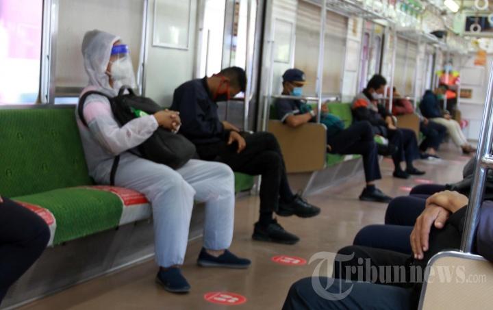Penumpang KRL Commuter Line Gunakan APD