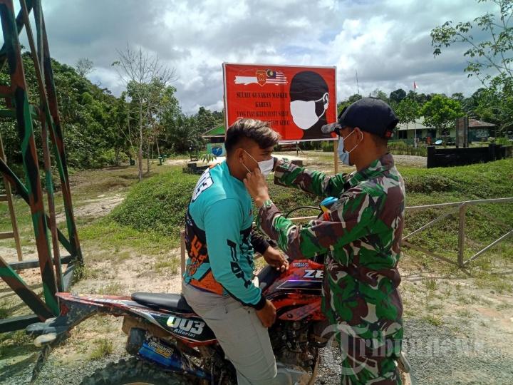 Satgas Pamtas RI-Malaysia Bagikan Masker kepada Pengendara Bermotor