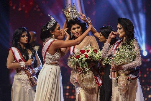 Mrs World Caroline Jurie melepas mahkota pemenang Mrs Sri Lanka Pushpika de Silva selama kontes kecantikan untuk wanita yang sudah menikah di Kolombo pada hari Minggu, 4 April 2021