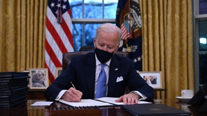 Presiden AS Joe Biden duduk di Oval Office saat dia menandatangani serangkaian perintah di Gedung Putih di Washington, DC, setelah dilantik di US Capitol pada 20 Januari 2021.