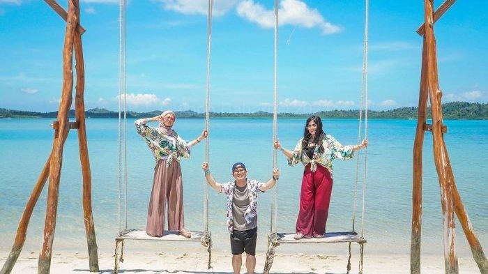 Pengunjung sedang bermain ayunan di area Pulau Ranoh