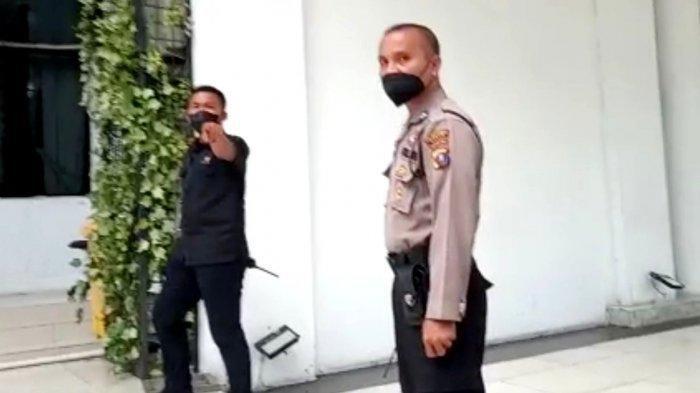 Seorang polisi dan pria berpakaian safari usir wartawan saat hendak wawancara di Balai Kota Medan, Rabu (14/4/2021). Keduanya tidak mengizinkan siapapun berada di areal Balai Kota.(HO)