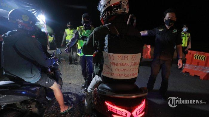 Petugas gabungan melakukan penyekatan pemudik di Pos Gamon, Karawang, Jawa Barat, Sabtu (8/5/2021) malam. Dalam penyekatan pemudik yang mayoritas pengendara roda dua tersebut, pemudik diarahkan untuk memutar balik menuju Jakarta, namun banyak pemudik yang menerobos penyekatan ini.