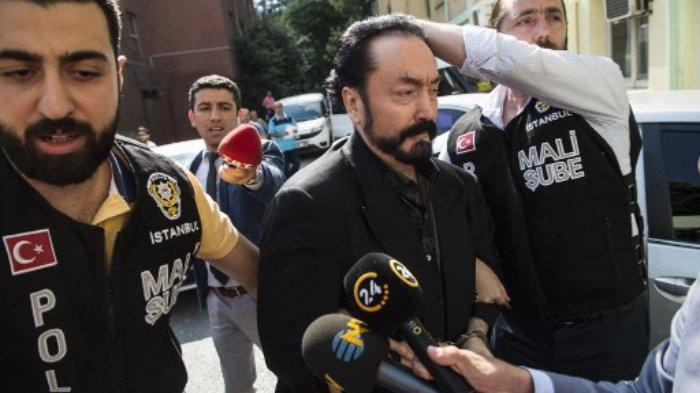 (FILES) Dalam foto file ini diambil pada 11 Juli 2018 petugas polisi Turki mengawal televangelist dan pemimpin sekte, Adnan Oktar (tengah) di Istanbul, saat dia ditangkap atas tuduhan penipuan. Pengadilan Turki pada 11 Januari 2021 menghukum seorang televangelis Muslim yang mengelilingi dirinya dengan wanita berpakaian minim yang dia sebut