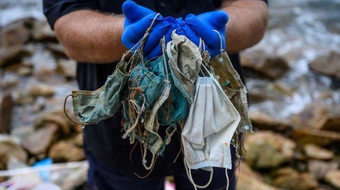 ILUSTRASI - Foto tertanggal 13 Mei 2020 menunjukkan Gary Stokes pendiri LSM lingkungan hidup Oceans Asia, memegang sampah masker sekali pakai yang berserakan di Discovery Bay di Pulau Lantu yang terpencil di Hong Kong. Selain berserakan di sepanjang garis pantai, beberapa sampah masker sekali pakai juga hanyut ke laut.