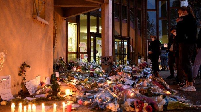 FOTO: Orang-orang berdiri di depan bunga dan lilin di samping plakat bertuliskan 'Saya seorang guru, saya Samuel' di pintu masuk sekolah menengah di Conflans-Sainte-Honorine, 30 km barat laut Paris, pada 17 Oktober 2020, setelah seorang guru dipenggal lantaran membawa karikatur Nabi Muhammad dalam kelasnya.