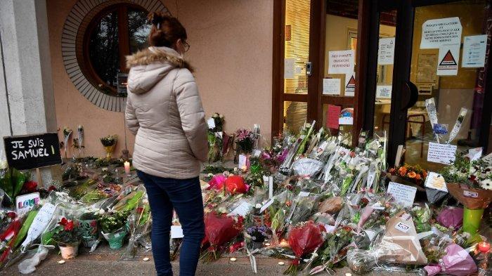 FOTO: Seorang wanita melihat karangan bunga di pintu masuk sekolah menengah di Conflans-Sainte-Honorine, 30 km barat laut Paris, pada 17 Oktober 2020, setelah tewasnya seorang guru dipenggal oleh penyerang lantaran membawa karikatur Nabi Muhammad