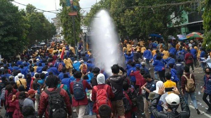 Sejumlah mahasiswa berlarian saat water cannon menyenmprotkan air saat demonstrasi mahasiswa menolak omnibus law di depan Gedung DPRD Kota Sukabumi, Jawa Barat, Kamis (8/10/2020).