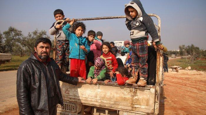Rombongan anak-anak diangkut menggunakan kendaraan di sebuah kamp di Suriah.