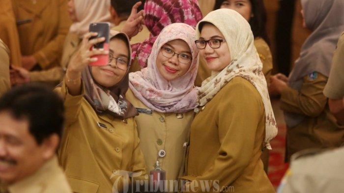 Pegawai Negeri Sipil (PNS) saat berselfie ditengah kerumunan pegawai saat acara halal bihalal dengan sejumlah Pegawai Negeri Sipil (PNS) di Gedung Balaikota, Jakarta Pusat, Senin (10/6/2019). Acara tersebut diikuti oleh ratusan pegaiwai balaikota Jakarta.