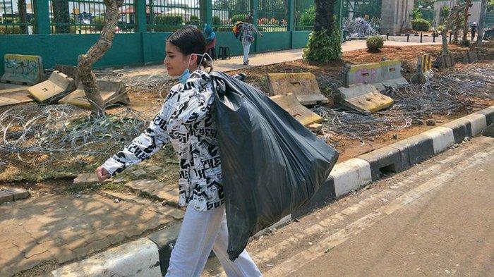 Selebgram Awkarin membawa kantong plastik berisikan sampah di depan gedung DPR RI, Senayan, Jakarta Pusat, Kamis (26/9/2019).