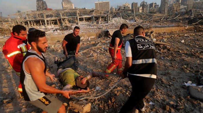 Kumpulan pria yang sedang menandu korban akibat Ledakan di Beirut, Lebanon, Selasa (4/8/2020).
