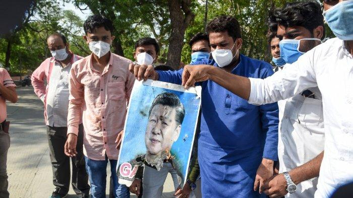 FOTO: Anggota Persatuan Pelajar Nasional India (NSUI) memegang poster Presiden Cina Xi Jinping yang terbakar sebagian saat demonstrasi anti-Tiongkok di Ahmedabad pada 18 Juni 2020.