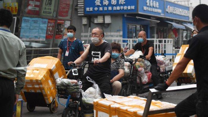 Orang-orang membawa barang keluar dari pasar makanan laut Jingshen di Beijing pada 13 Juni 2020. Pasar ditutup untuk desinfeksi dan penyelidikan pada 12 Juni setelah ditemukan bahwa seorang pasien virus corona yang baru diidentifikasi telah mengunjunginya.