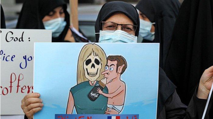 IRAK - Para pengunjuk rasa Irak membawa poster selama demonstrasi menentang Presiden Prancis Emmanuel Macron di depan kedutaan besar Prancis di Baghdad pada 26 Oktober 2020. Seruan untuk memboikot barang-barang Prancis berkembang di dunia Arab dan sekitarnya, setelah Presiden Emmanuel Macron mengkritik kaum Islamis dan bersumpah tidak untuk