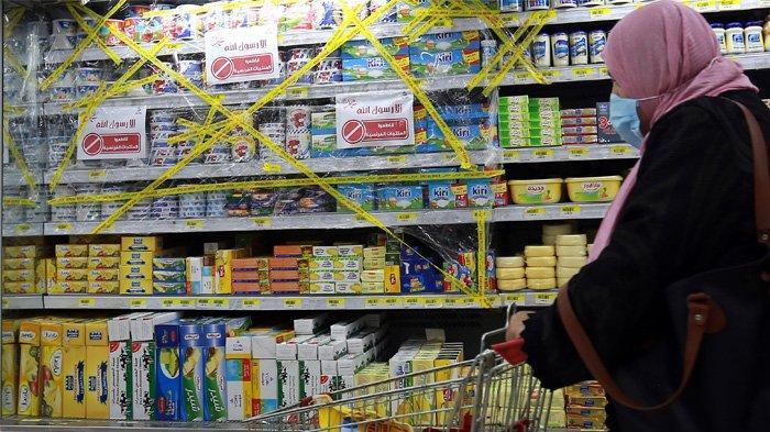 ORDANIA - Seorang pembelanja berjalan melewati produk Prancis yang disegel di balik penutup plastik di rak di supermarket di ibu kota Yordania, Amman, selama boikot produk Prancis pada 26 Oktober 2020. Seruan untuk memboikot barang-barang Prancis berkembang di dunia Arab dan sekitarnya, setelah Presiden Emmanuel Macron mengkritik kaum Islamis dan bersumpah untuk tidak