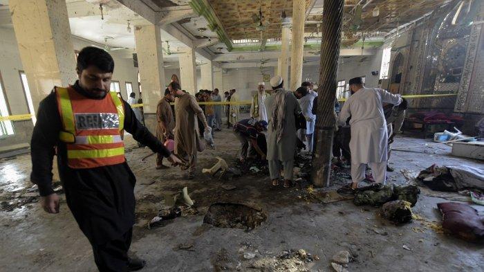 FOTO: Sejumlah petugas memeriksa lokasi ledakan di sebuah madrasah di Peshawar pada 27 Oktober 2020. Sedikitnya empat siswa tewas dan puluhan lainnya luka-luka pada 27 Oktober ketika sebuah bom meledak saat pelajaran di kelas sedang berlangsung di Pakistan, kata para pejabat.