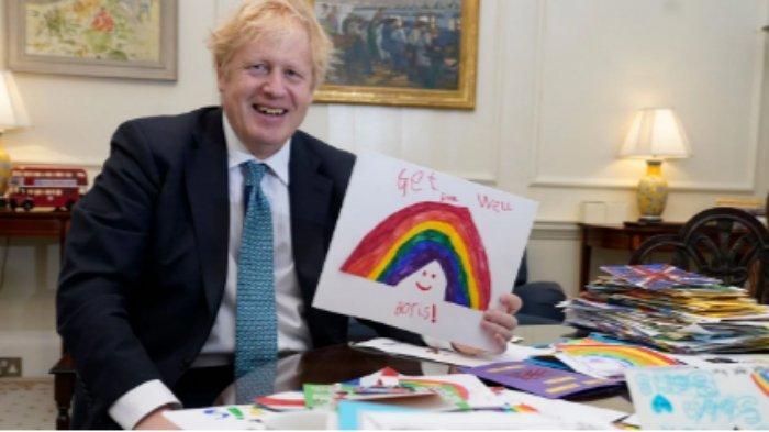 Boris Johnson saat menunjukkan kartu ucapan cepat sembuh yang diberikan anak-anak (AFP)