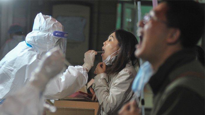 Foto yang diambil pada 13 Oktober 2020 ini menunjukkan seorang petugas kesehatan mengambil sampel dari seorang penduduk untuk dites virus corona COVID-19 sebagai bagian dari program pengujian massal menyusul wabah baru virus korona di Qingdao, di provinsi Shandong timur China. (STR / AFP / China OUT)