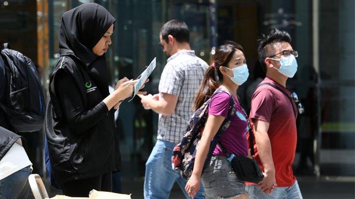 Seorang sukarelawan dari Kementerian Komunikasi Singapura bersiap untuk mengumpulkan umpan balik dari anggota masyarakat mengenai situasi wabah virus coronavirus saat ini saat istirahat makan siang di distrik bisnis keuangan Raffles Place di Singapura pada 5 Februari 2020. Roslan RAHMAN / AFP