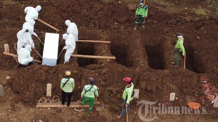 Petugas mengubur jenazah terkait Covid-19 di Taman Pemakaman Umum (TPU) Srengseng Sawah, Jakarta Selatan, Jumat (15/1/2021). Media luar negeri mulai menyoroti penanganan pandemi Covid-19 di Indonesia setelah seorang pasien positif yang ditolak 10 rumah sakit meninggal dunia.
