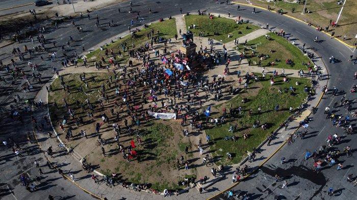 Pemandangan udara dari protes terhadap polisi Chili setelah Antony Araya, 16, jatuh dari jembatan ketika polisi berusaha menangkapnya selama bentrokan hari Jumat, di alun-alun Plaza Italia di Santiago pada 3 Oktober 2020. Kantor Kejaksaan Agung Chili mengumumkan pada hari Sabtu penangkapan seorang petugas polisi atas tuduhan