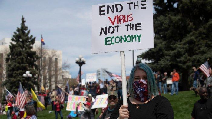 Demonstran berkumpul di depan gedung Colorado State Capitol untuk memprotes kebijakan penanganan coronavirus yang memaksa orang tinggal di rumah, selama rapat umum