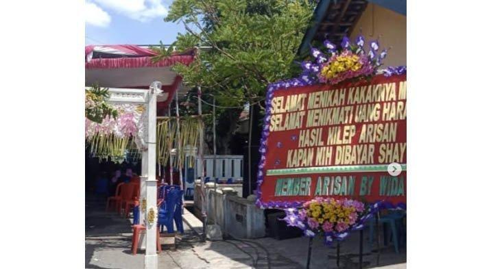 Foto karangan bunga bernada menyindir arisan bodong di acara pernikahan di Sragen. Viral di media sosial.