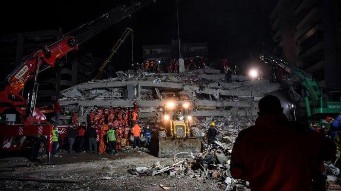 FOTO: Tim penyelamat mencari korban di antara puing-puing bangunan yang runtuh setelah gempa bumi dahsyat melanda pantai barat Turki dan sebagian Yunani, pada 30 Oktober 2020.