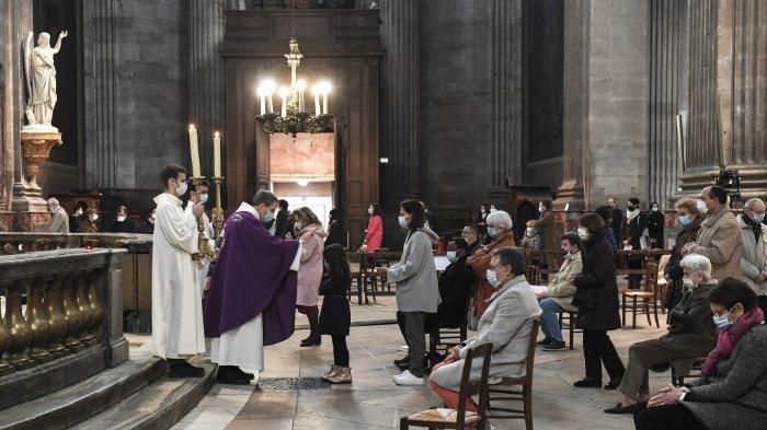 FOTO: Orang-orang menghadiri kebaktian di gereja Saint-Sulpice di Paris pada 29 November 2020 saat misa dilanjutkan di Prancis menyusul pemerintah melonggarkan pembatasan penguncian Covid-19 dengan hanya 30 orang yang diizinkan per gereja.