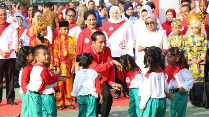 Presiden Jokowi, Ibu Iriana, beserta Menteri Yohana Yembesi duduk bersama anak-anak dalam rangka perayaan Hari Anak Nasional 2017 di Pekanbaru, Riau.