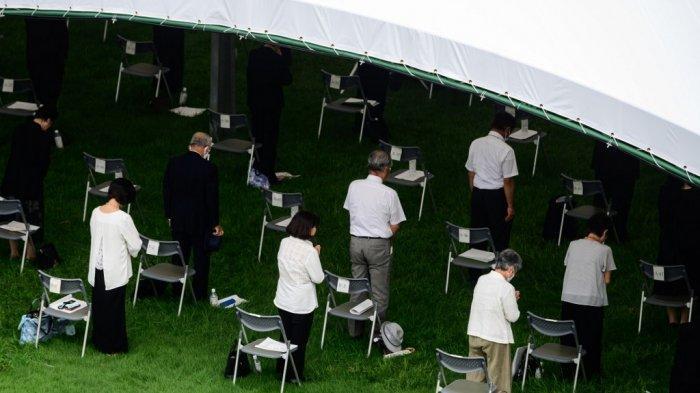 Para penyintas dan keluarga yang berduka ambil bagian dalam doa hening sambil menjaga jarak sosial selama upacara peringatan 75 tahun korban bom atom di Peace Memorial Park di Hiroshima pada 6 Agustus 2020. Jepang pada 6 Agustus 2020 menandai 75 tahun sejak pertama di dunia. Serangan bom atom, dengan pandemi COVID-19 virus corona memaksa diadakannya upacara tahunan untuk memperingati para korban. (Philip FONG / AFP)