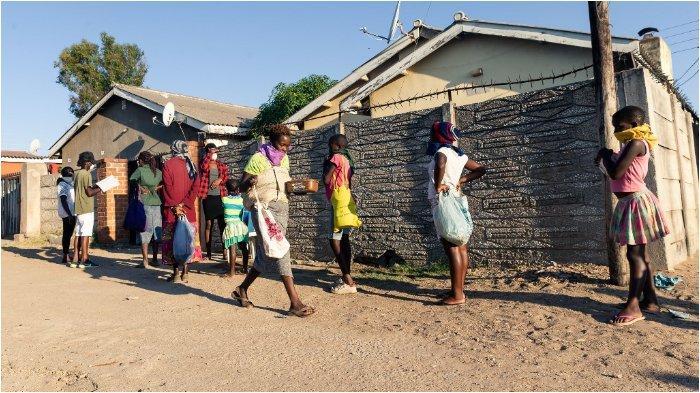 (ILUSTRASI Pandemi Covid-19 bisa picu kelaparan) Antrian orang-orang yang membutuhkan dengan piring di tangan di luar rumah Samantha Murozoki di Chitungwizaon pada 5 Mei 2020, di mana dia memberi makan orang kurang mampu makanan gratis selama pemerintah memberlakukan periode penguncian COVID-19 coronavirus di Zimbabwe. Dengan bantuan sukarelawan, Samantha Murozoki menyajikan lebih dari 100 makanan hangat per hari dari rumahnya kepada keluarga kurang mampu yang pendapatan rumah tangganya telah terputus oleh penutupan semua pasar informal selama penutupan.