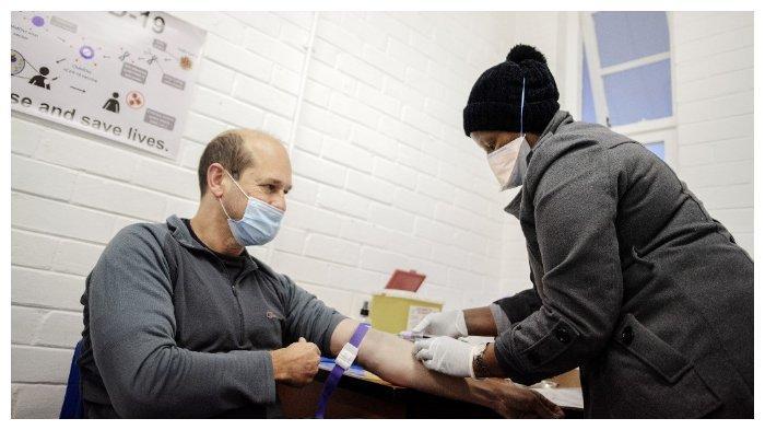 Tenaga medis (kanan) mengambil sampel darah Profesor Francois Venter (kiri) sebelum pria itu menerima vaksin Covid-19 eksperimental di  Unit Penelitian Patogen Meningeal dan Pernapasan (RMPRU) di RS Chris Hani Baragwanath Hospital, Soweto, Afrika Selatan, Selasa (14/7/2020).