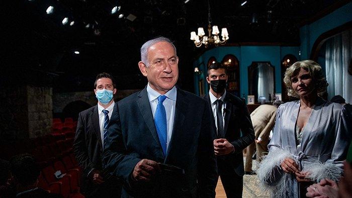 Perdana Menteri Israel Benjamin Netanyahu (kiri) bertemu aktris Israel Carmit Mesilati Kaplan (kanan) selama kunjungan ke teater Khan menjelang pembukaan kembali sektor budaya setelah penutupan yang diberlakukan Covid-19, pada 23 Februari 2021 di Yerusalem. Netanyahu dikabarkan telah meminta kepada Presiden AS Joe Biden agar tidak mencabut sanksi ICC yang sedang menyelidiki kasus kejahatan perang Israel dalam pencaplokan wilayah Palestina.