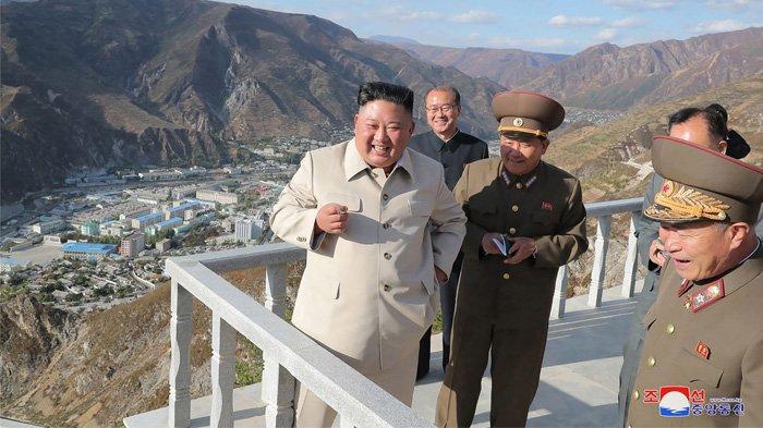 Gambar tak bertanggal yang dirilis dari Kantor Berita Pusat Korea (KCNA) resmi Korea Utara pada 14 Oktober 2020 menunjukkan pemimpin Korea Utara Kim Jong Un (kiri) sedang memeriksa lokasi rehabilitasi di daerah Komdok di Provinsi Hamgyong Selatan, yang rusak akibat topan. (KCNA VIA KNS / AFP)