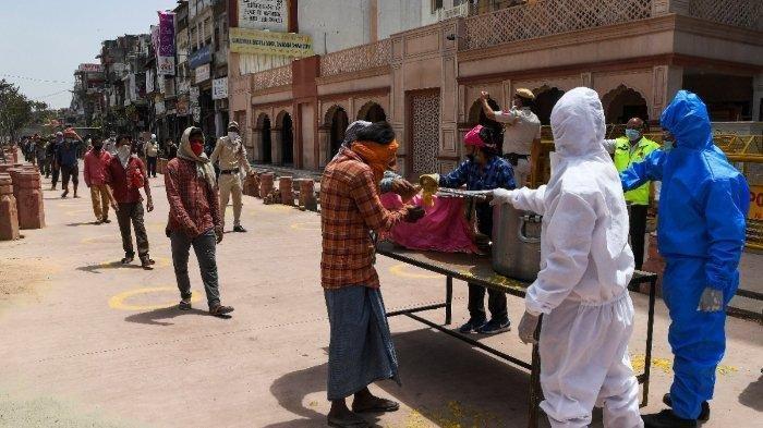 Relawan dari sebuah kuil Sikh mendistribusikan makanan gratis kepada para tunawisma selama penguncian nasional yang diberlakukan pemerintah sebagai tindakan pencegahan terhadap penyebaran virus corona COVID-19 di New Delhi pada 15 April 2020.