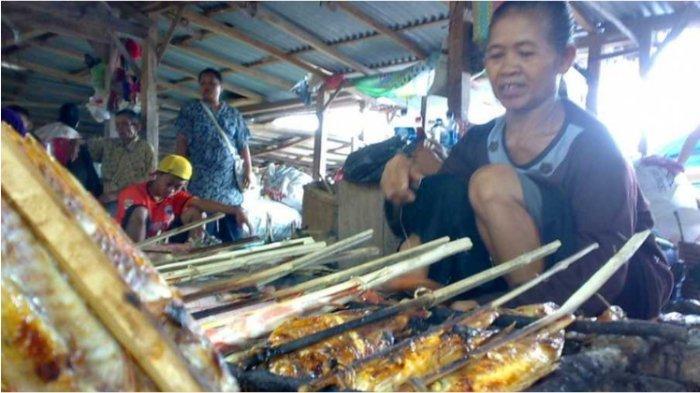Seorang pedagang saat membakar ikan air tawar hasil tangkapan nelayan di Waduk Kedung Ombo, Grobogan, Jawa Tengah, Minggu, 3 Agustus 2014. (beritasatu.com/Danung Arifin )